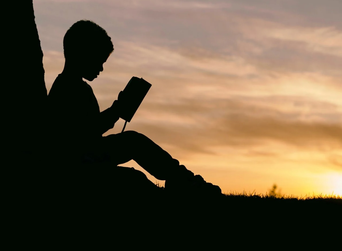 Child reading a book at sunset