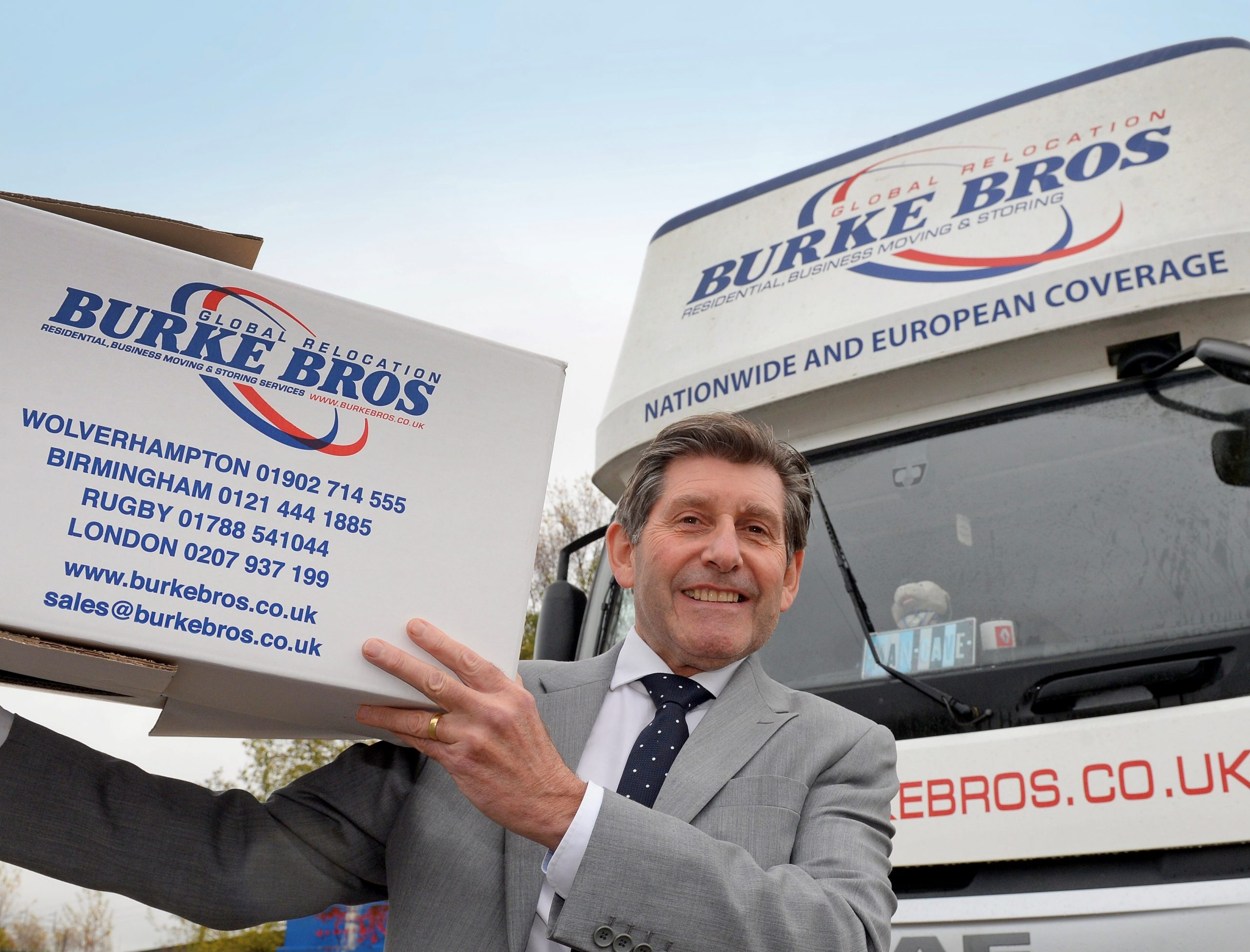 Gary Burke with boxes next to a company van
