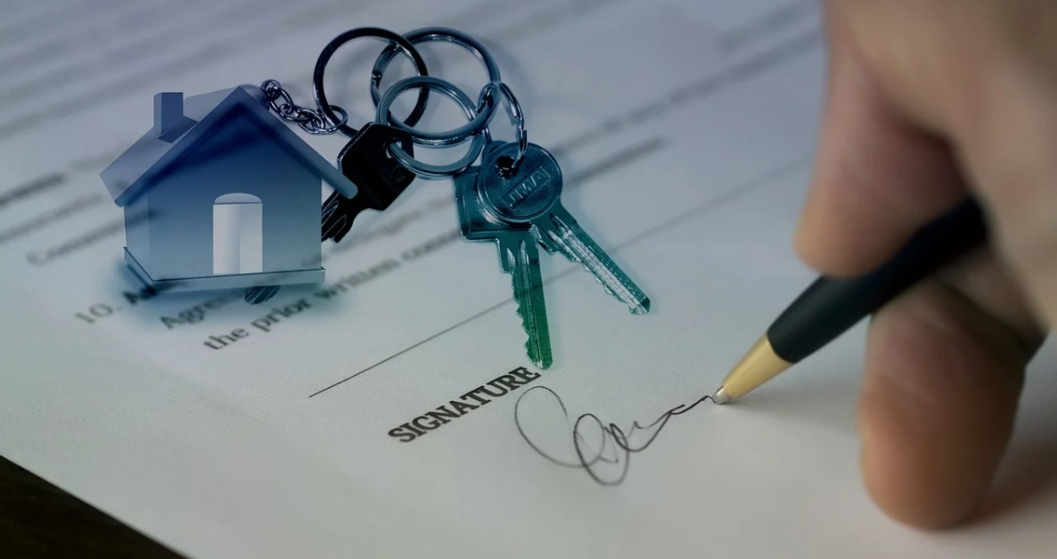 A document being signed next to keys to a new house