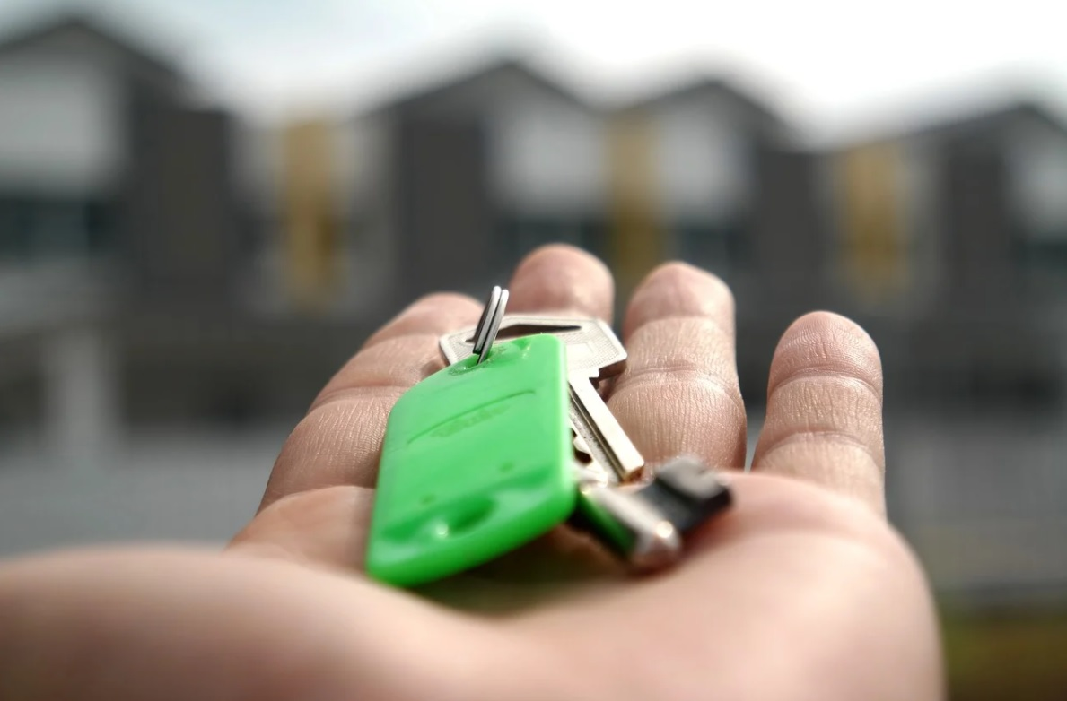 Hand holding a set of keys in front of a property